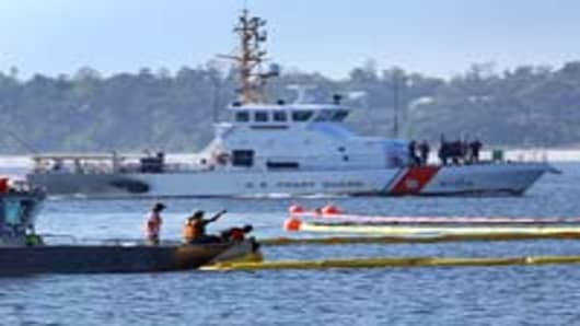 A Coast Guard boat passes as workers put oil containment booms in the water as they try to protect the inlet waterways from the Deepwater Horizon oil spill in the Gulf of Mexico on June 7, 2010 in Pensacola, Florida. Early reports indicate that BP's latest plan to stem the flow of oil from the site of the Deepwater Horizon incident may be having some success.