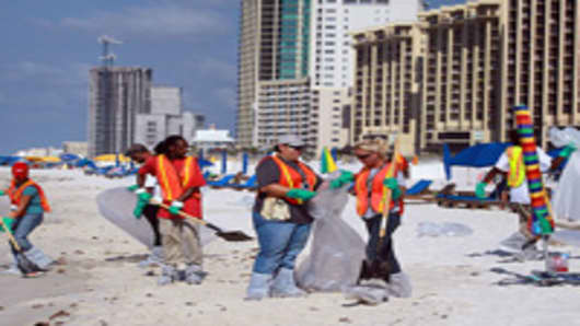 Workers clean up oil patches and tar that washed up on the beach from the oil spill in the Gulf of Mexico on June 8, 2010 in Orange Beach,