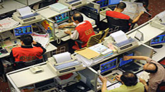 Traders sit at their desks at the Stock Exchange in Hong Kong.