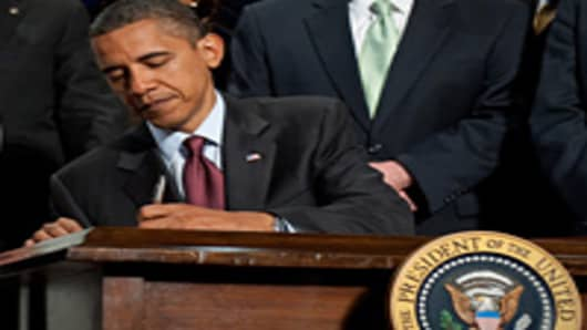 President Barack Obama signs the Dodd-Frank Wall Street Reform and Consumer Protection Act on July 21, 2010.