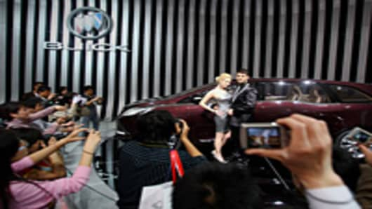 Two models stand beside Buick Business concept car during the Beijing Auto Show.