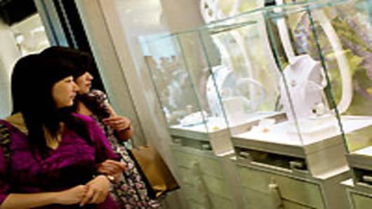 Two women look at a jewelry display in a luxury shopping mall in Shanghai. Fol