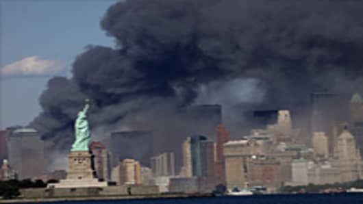 The view from Jersey City, NJ of The Statue of Liberty and the burning remains of the World Trade Center after two airliners crashed into the buildings on Tuesday morning, September 11, 2001.