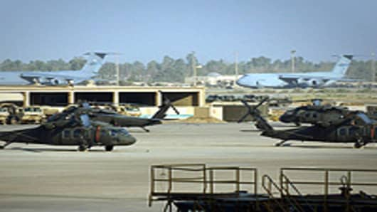 US Army Blackhawk helicopters sit on the tarmac with US Air Force C5A transport jets in the background at Baghdad International Airport.
