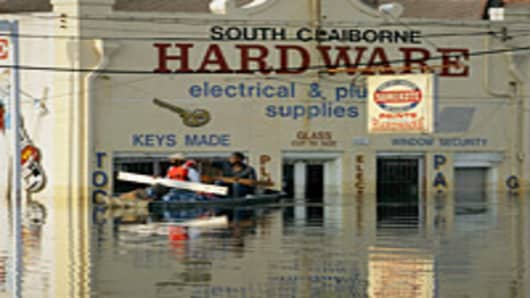 Two men use boards as paddles as they row a boat loaded with water bottles past a hardware store in New Orleans' Mid-City district, which remains submerged in some 8-12 feet of water in the aftermath of Hurricane Katrina.