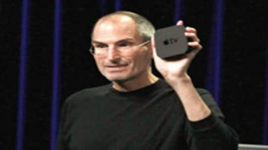 Apple CEO Steve Jobs holds the new, smaller Apple TV device as speaks during an Apple Special Event in San Francisco.