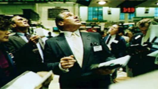 Traders on the floor of the New York Stock Exchange floor watch monitors on October 10, 1987.