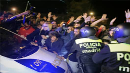 Demonstrators block a police car on the parking lot of the Madrid transport bus company during the general strike held in whole Spain in Madrid as unions launched a 24-hour general strike all around Spain to protest tough government labor reforms and austerity measures.