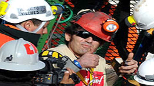 Chilean miner Alex Vega Salazar gives a thumbs up upon exiting the Fenix capsule as the tenth miner to be brought to the surface, on October 13, 2010.