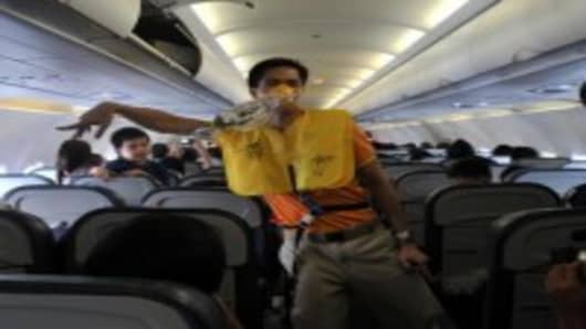 A cabin crew member of budget airline Cebu Pacific performs a dance as part of the inflight safety demonstration during a flight between Manila and Davao City