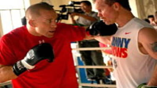 UFC welterweight champion Georges St-Pierre (L) of Canada spars with Philippine boxing star Manny Pacquaio's trainor Freddie Roach during a visit to Pacquaio's training at a gym in Manila on September 24, 2010.