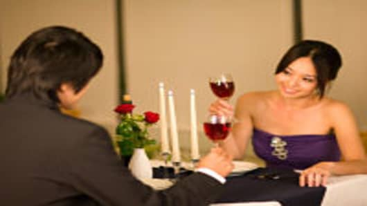 Young couple looking at each other and holding a glass of red wine.
