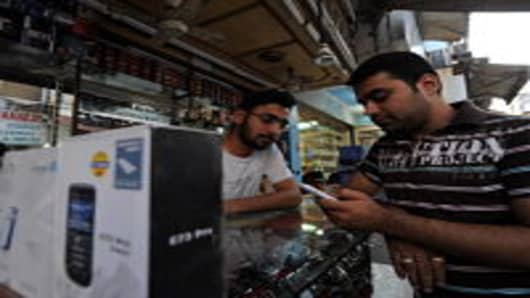 An Indian man checks a new mobile phone at a shop in New Delhi on May 12, 2010.