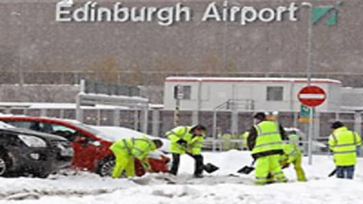 Workmen clear snow from Edinburgh Airport car park on December 1, 2010 in Edinburgh, Scotland. Freezing weather conditions and heavy snow have forced Scotland's main airport to close for the day.