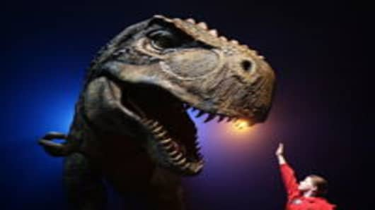 A girl gestures towards a Tyrannosaurus Rex at the media call for Walking With Dinosaurs - The Arena Spectacular at The Entertainment Quarter in Sydney, Australia.