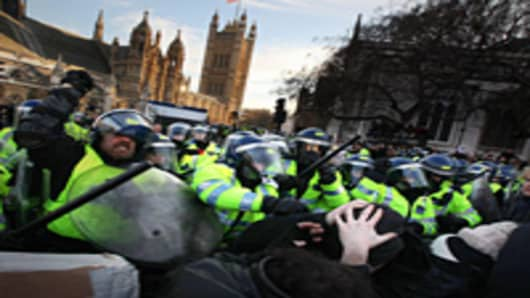 Angry demonstrators clashed with police in a student protest outside parliament as the coalition government faced its biggest test yet in a vote on proposals to triple university tuition fees.