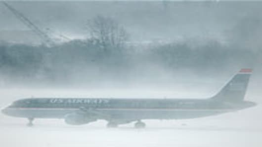 US Airways jet on the tarmac surrounded by blowing snow, Philadelphia International Airport.