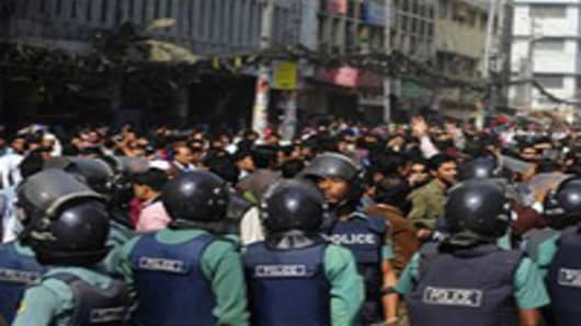Bangladeshi police look on as a crowd of investors shout slogans during a protest in front of The Dhaka Stock Exchange in Dhaka.