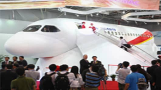 Visitors inspect the C919 prototype at an aviation exhibition during the Zhuhai Airshow.