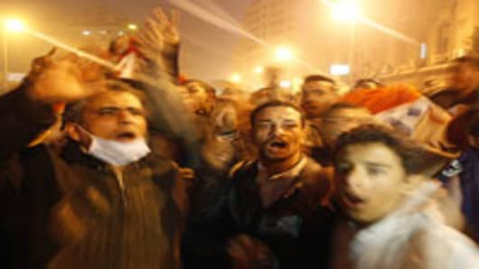 Egyptian demonstrators shout slogans next to burning police vehicles in Cairo on January 28, 2011.