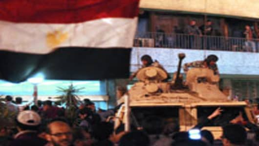Egyptian demonstrators demanding the ouster of President Hosni Mubarak, gather around the national television building guarded by members of the Presidential guard in Cairo on January 28, 2011.