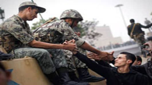 Marchers shake hands with Egyptian Army soldiers on tanks during a demonstration against President Hosni Mubarek in Tahrir Square January 29, 2010 in Cairo, Egypt. Egytian soldiers were for the most part interacting peacefully with the marchers in Tahrir Square during the afternoon hours.