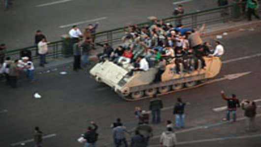 Protestors ride an armoured personnel carrier towards the Nile on January 29, 2011 in Cairo, Egypt. Tens of thousands of demonstrators have taken to the streets across Egypt in Cairo, Suez, and Alexandria to call for the resignation of President Hosni Mubarak.