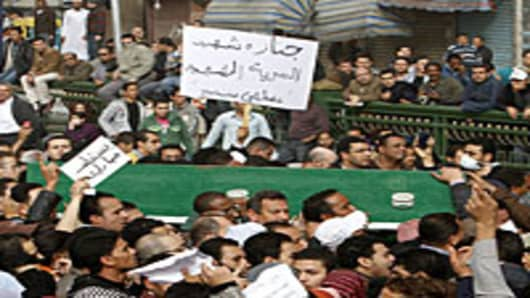 People carry the coffin of Egyptian demonstrator Mustafa Samer, during his funeral in Cairo on January 29, 2011.