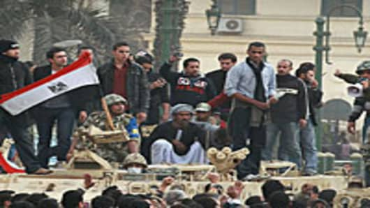 Protestors stand with a soldier as he waves an Egyptian flag on an army tank in Tahrir Square on January 29, 2011 in Cairo, Egypt.