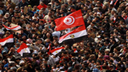 Egyptian anti-government protesters wave a Tunisian flag along with national banners during continuing demonstrations in Cairo's landmark Tahrir Square.