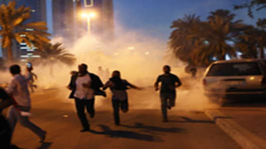 Protesters run from a cloud of teargas during a clash with Bahraini security forces near the Pearl roundabout in Manama, Bahrain. Protesters said that the army fired on them with live rounds, followed by teargas which drove the demonstrators back. There are unconfirmed reports that there are four dead in the clashes.