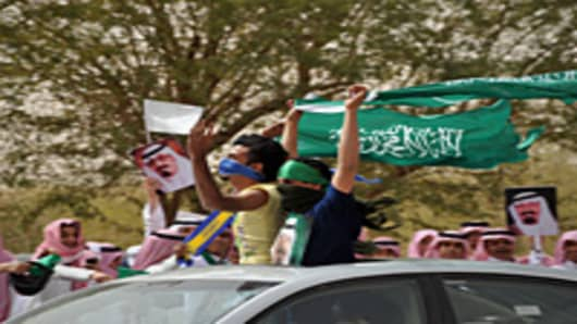Saudi youth wave their national flag as they celebrate the return of King Abdullah bin Abdul Aziz in the Saudi capital Riyadh.