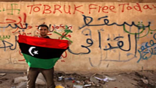 A Libyan anti-government protester holds his old national flag in front of a wall covered with graffiti against Libyan leader Moamer Kadhafi in the eastern city of Tobruk.