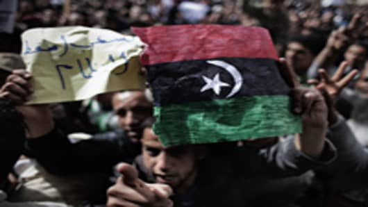A Libyan demonstrator holds his country's old flag during a protest in the eastern city of Tobruk.