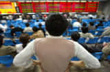 A local investor watches the share-prices index display at a stock brokerage in Shanghai.
