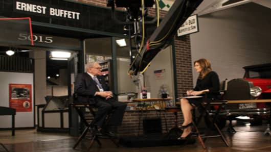 Warren Buffett is interviewed by CNBC's Becky Quick in 2011 in front of a mock-up of the Buffett family grocery store in Omaha where he worked as a child.