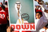 A Bahraini anti-regime protester holds up a poster with a caricature image of Prime Minister Khalifa bin Salman al-Khalifa calling him a &quot;war criminal&quot; during a demonstration in the capital Manama.