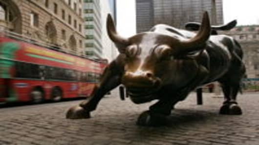 A tour bus passes the Wall Street bull in the financial