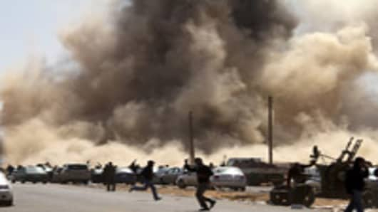 Libyan rebel fighters take cover as a bomb dropped by an airforce fighter jet explodes near a checkpoint on the outskirts of the oil town of Ras Lanuf on March 7, 2011. AFP PHOTO/MARCO LONGARI (Photo credit should read MARCO LONGARI/AFP/Getty Images)