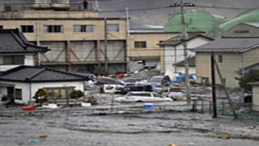 A tsunami, tidal wave smashes vehicles and houses at Kesennuma city in Miyagi prefecture, northern Japan. A massive 8.9-magnitude earthquake shook Japan, unleashing a powerful tsunami that sent ships crashing into the shore and carried cars through the streets of coastal towns.