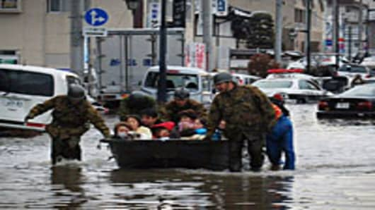 Soldiers pull a boat across floodwater as they help to evacuate residents of Tagajo city, Miyagi