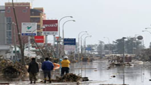 People stand amid debris on a flooded street in Iwanuma city, Miyagi prefecture
