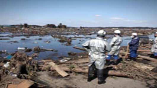 Rescue workers look over an area flooded by the tsunami in Minamisoma, Fukushi