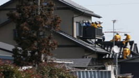 Members of a rescue team climb into a house