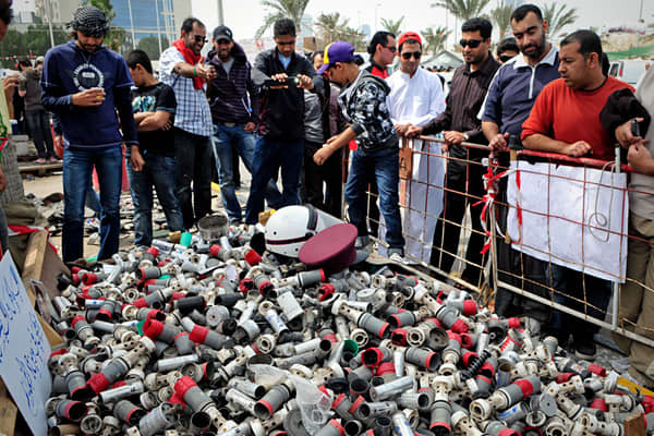 Bahraini anti-government look at spent gas canisters, stun grenades, rubber bullets all piled up in Pearl Square, the epicentre of the anti government movement, in Manama on March 14, 2011, a day after Bahraini police clashed with demonstrators trying to occupy Manama's banking centre, as protests spread from a peaceful sit-in to the heart of the strategic Gulf state's business district.