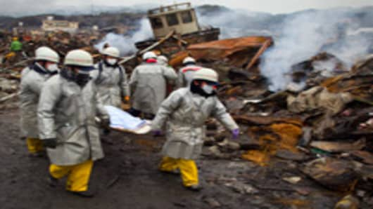 Rescue workers carry a body from the rubble of a village destroyed by the devastating earthquake, fires and tsunami March 16, 2011 in Kesennuma, Miyagi province, Japan.