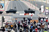 Anti-government protestors open their arms in front of military vehicles near Pearl Square in Bahraini capital Manama, on March 16, 2011, after Bahraini police killed at least two protesters and wounded dozens more as they assaulted a peaceful protest camp in the capital&#039;s Pearl Square, an opposition party official said. AFP PHOTO/STR (Photo credit should read -/AFP/Getty Images)