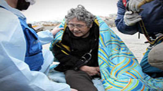 80-year-old Sumi Abe is rescued from her destroyed house nine days after the 9.0 magnitude earthquake and tsunami on March 20, 2011 in Ishinomaki, Miyagi, Japan.