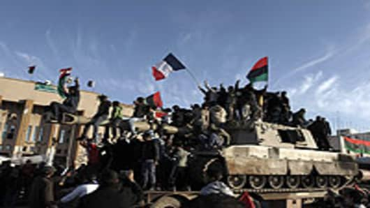 Libyans wave the French flag as they parade on a 155mm Howitzer belonging to Muammar Gaddafi forces in the eastern rebel-held city of Benghazi on March 21, 2011.