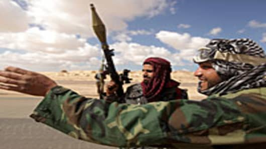 Lybian rebels deploy for a second day on several kilometres from the key city of Ajdabiya to try to attack government forces that have encircled the town on March 22, 2011.